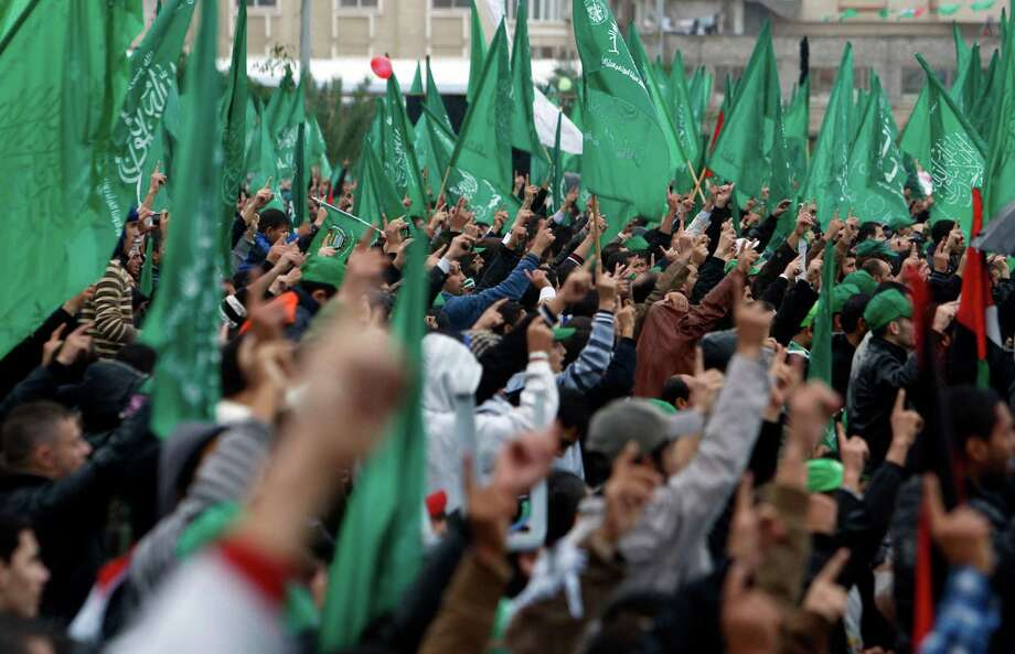Palestinian Hamas activists raise their fingers while chanting Islamic slogans as other wave green Islamic flags during a rally to commemorate the 25th anniversary of the Hamas militant group, in Gaza city, Saturday, Dec. 8, 2012.  Hamas chief Khaled Mashaal is expected to speak at Saturday's rally in Gaza City after entering the seaside strip a day earlier after a long exile from Palestinian territory. (AP Photo/Adel Hana) Photo: Adel Hana