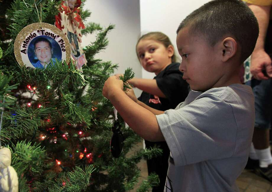 Natalie Vargas, 3, places a Christmas ornament with a photo of her father, Roland Vargas on it on the Christmas tree as her cousin Evan Marcus helps her during the 18th annual Crime Victims Memorial Remembrance Tree Lighting Ceremony in the City Hall annex, Saturday, Dec. 8, 2012, in Houston. Roland Vargas and his cousin Lee Hernandez were killed a year and a half ago outside of a club. Photo: Karen Warren, Houston Chronicle / © 2012  Houston Chronicle