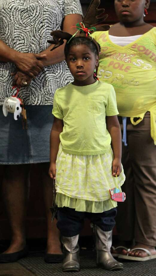 Carolyn Gray, 3, holds an ornament in remembrance of her uncle Curtis Steward III, who was killed three months ago at a club breaking up a fight, during the 18th annual Crime Victims Memorial Remembrance Tree Lighting Ceremony in the City Hall annex, Saturday, Dec. 8, 2012, in Houston. Parents of murdered children and surviving family members of homicide placed ornaments on the tree for their loved ones, which remains on display for the holiday season. Photo: Karen Warren, Houston Chronicle / © 2012  Houston Chronicle