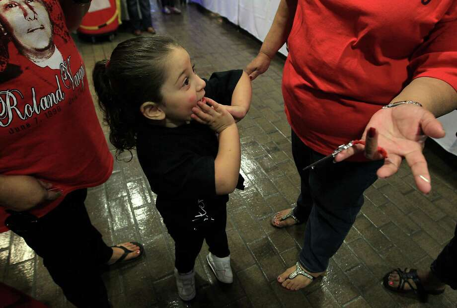 Natalie Vargas, 3, reacts as she sees a Christmas ornament with a photo of her father, Roland Vargas,  during the 18th annual Crime Victims Memorial Remembrance Tree Lighting Ceremony in the City Hall annex, Saturday, Dec. 8, 2012, in Houston. Roland Vargas and his cousin Lee Hernandez were killed a year and a half ago outside of a club. Photo: Karen Warren, Houston Chronicle / © 2012  Houston Chronicle