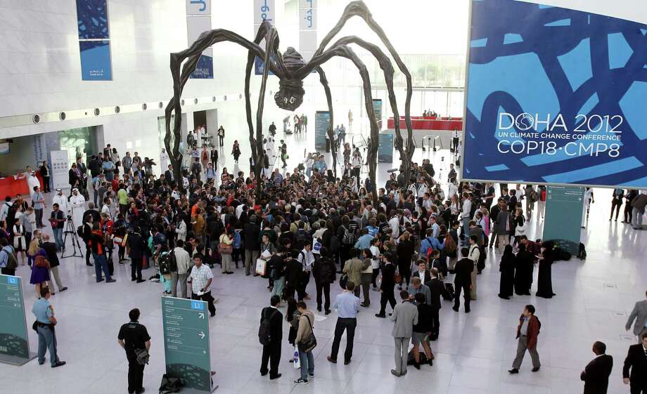 Local and international activists march inside a conference center under a giant statue of a spider to demand urgent action to address climate change at the U.N. climate talks in Doha, Qatar, Friday, Dec. 7, 2012. A dispute over money clouded U.N. climate talks Friday, as rich and poor countries sparred over funds meant to help the developing world cover the rising costs of mitigating global warming and adapting to it. (AP Photo/Osama Faisal) Photo: Osama Faisal, STR / AP