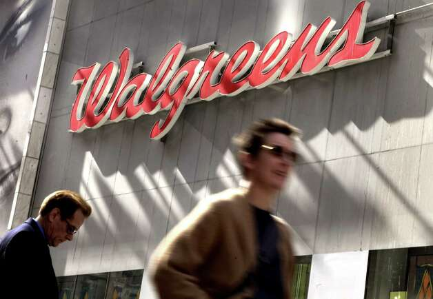 In this Wednesday, Oct. 17, 2012, photo. people pass the Walgreens store in New York's Times Square. Walgreens wants to reward customers for merely taking a walk, and Rite Aid will help cover trial gym memberships for some of its frequent shoppers. All the national drugstore chains now offer a free customer loyalty program loaded with incentives to use their cards. Walgreen Co., the nation's largest drugstore chain, became the latest when it unveiled its Balance Rewards program in September 2012. (AP Photo/Richard Drew) Photo: Richard Drew / AP