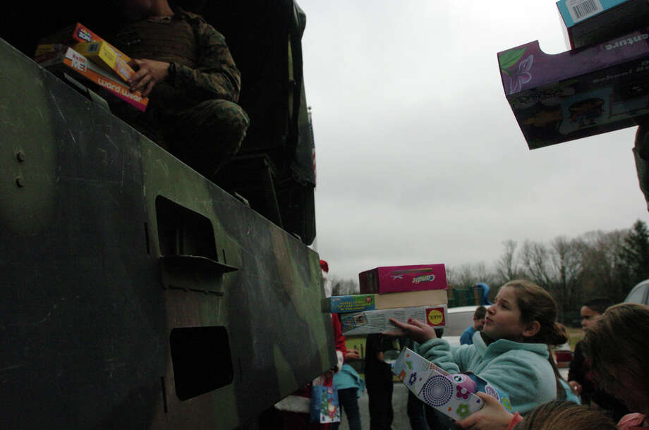 Marielle Povinelli, 9, helps to load a truck for the Toys for Tots annual toy drive at the Banksville Community House in Greenwich, Conn., Dec. 8, 2012. Photo: Keelin Daly / Stamford Advocate Riverbend Stamford, CT