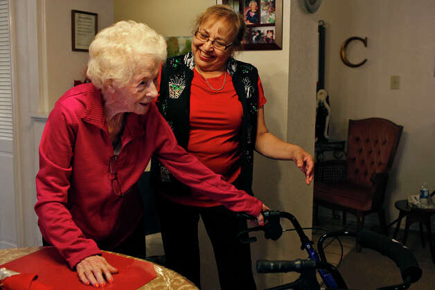 Dygert helps Golden Casa resident Linnie Thuesen, 109, move from the dining room cover to her seat in the living room at the facility. Photo: Lisa Krantz, San Antonio Express-News / © 2012 San Antonio Express-News