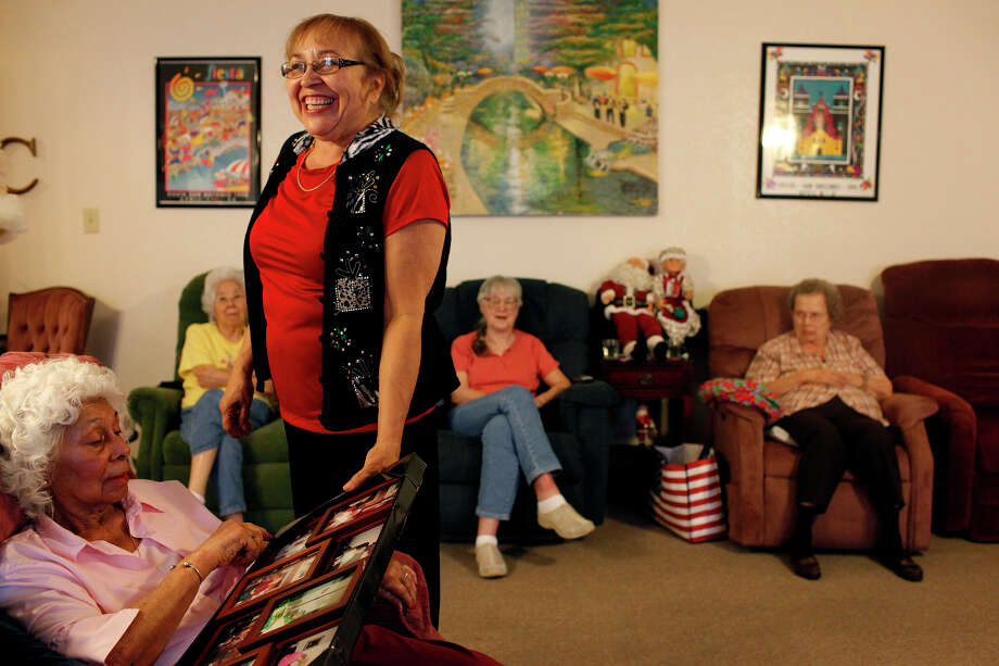 Diana Dygert, the co-owner and administrator of The Golden Casa, shows resident Hilda Colon, 79, a collage  at the assisted living home in San Antonio on Saturday, Dec. 8, 2012. The Editorial Board encourages the City Council to approve the boarding-home ordinance. Photo: Lisa Krantz, San Antonio Express-News / © 2012 San Antonio Express-News