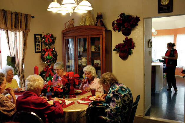 Residents of The Golden Casa eat lunch while Diana Dygert, the co-owner and administrator of the assisted living home, right, prepares their medications in San Antonio on Saturday, Dec. 8, 2012. Photo: Lisa Krantz, San Antonio Express-News / © 2012 San Antonio Express-News