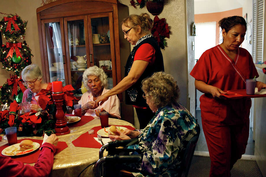 Diana Dygert (standing, center), co-owner and administrator of the Golden Casa assisted-living home, gives medication to resident Hilda Colón, 79, while she has lunch with fellow residents Carol McGhee, 70 (left), Eunice Miller, 94. Photo: Lisa Krantz, San Antonio Express-News / © 2012 San Antonio Express-News