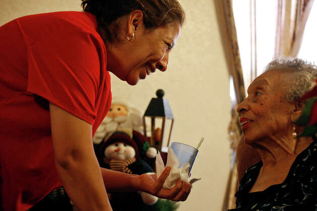 Assistant manager Maria Trevino, left, encourages resident Salome Jolly, 89, as Trevino assists her with a glass of Ensure at The Golden Casa, an assisted living home in San Antonio on Saturday, Dec. 8, 2012. Photo: Lisa Krantz, San Antonio Express-News / © 2012 San Antonio Express-News