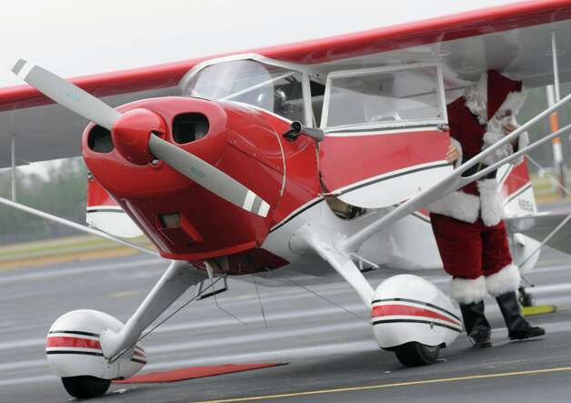 Santa hops out of a 1937 Monocoupe plane for the Sixth Annual Christmas Toy Airlift Saturday, Dec. 8, 2012 at the Chesterfield Airport in Chesterfield County, Va.  Donations of toys and gifts for veterans were flown in from across the Mid-Atlantic during the event, a project of the Virginia Chapter Ninety-Nines, an organization of women pilots. Photo: Patrick Kane, Associated Press / The Progress-Index