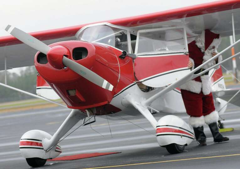 Santa hops out of a 1937 Monocoupe plane for the Sixth Annual Christmas Toy Airlift Saturday, Dec. 8