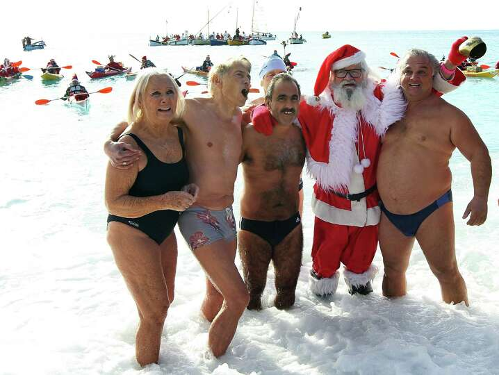 Beachgoers pose with a man wearing a Santa Claus costume as they stand in the Mediterranean Sea on D