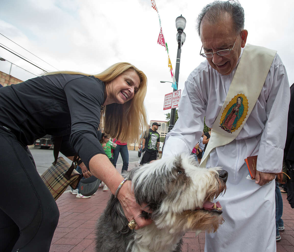 Deacon Tony Rivera, right, greets Polo, a bearded collie owned by Michelle Mika DeAtley, left, during the 26th annual Blessing of the Animals at Market Square on Saturday, Dec. 8, 2012.