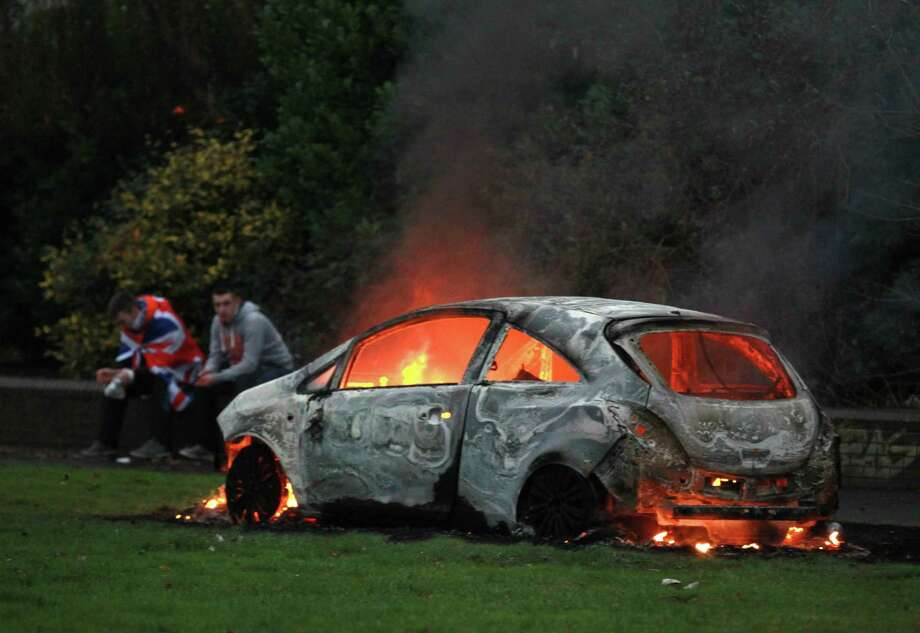 Loyalists sit near a burning car in east Belfast, Northern Ireland on December 8, 2012 after a march in protest against Belfast city council's decision to restrict the number of days the Union Flag will be flown over the city hall. Protests have broken out since Belfast city councillors voted to restrict the number of days the Union Flag will fly above City Hall from everyday, to 17, meaning it will be taken down for the first time since the building opened in 1906. Police said around 1,000 people rioted in Belfast after the controversial Union flag vote on December 3, with 15 officers, two security workers and a press photographer were injured during the clashes. AFP PHOTO/ PETER MUHLYPETER MUHLY/AFP/Getty Images Photo: PETER MUHLY, AFP/Getty Images / AFP