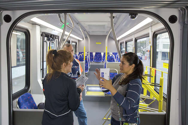 "VIA representative Sabrina Polanco, right, shows off a VIA Primo bus to Claudia Ruibal, front left, and LTC John Ruibal during a ""Better Block"" event at 300 W. Commerce on Saturday, Dec. 8, 2012. The organizers and city hope to promote more pedestrian friendly activities with sidewalk cafes and closing down some of the lanes on the road to make it friendlier to walkers. It's part of an effort to help spark a renewed interest in parts of downtown that have struggled to be revitalized in recent years. MICHAEL MILLER / FOR THE EXPRESS-NEWS Photo: Michael Miller, For The Express-News / © San Antonio Express-News"