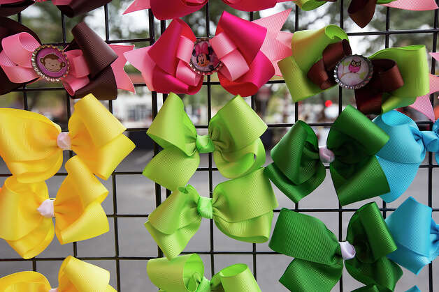 "Bows wait to be sold by Rosa Torres of Tots Boutique during a ""Better Block"" event at 300 W. Commerce on Saturday, Dec. 8, 2012. The organizers and city hope to promote more pedestrian friendly activities with sidewalk cafes and closing down some of the lanes on the road to make it friendlier to walkers. It's part of an effort to help spark a renewed interest in parts of downtown that have struggled to be revitalized in recent years. MICHAEL MILLER / FOR THE EXPRESS-NEWS Photo: Michael Miller, For The Express-News / © San Antonio Express-News"