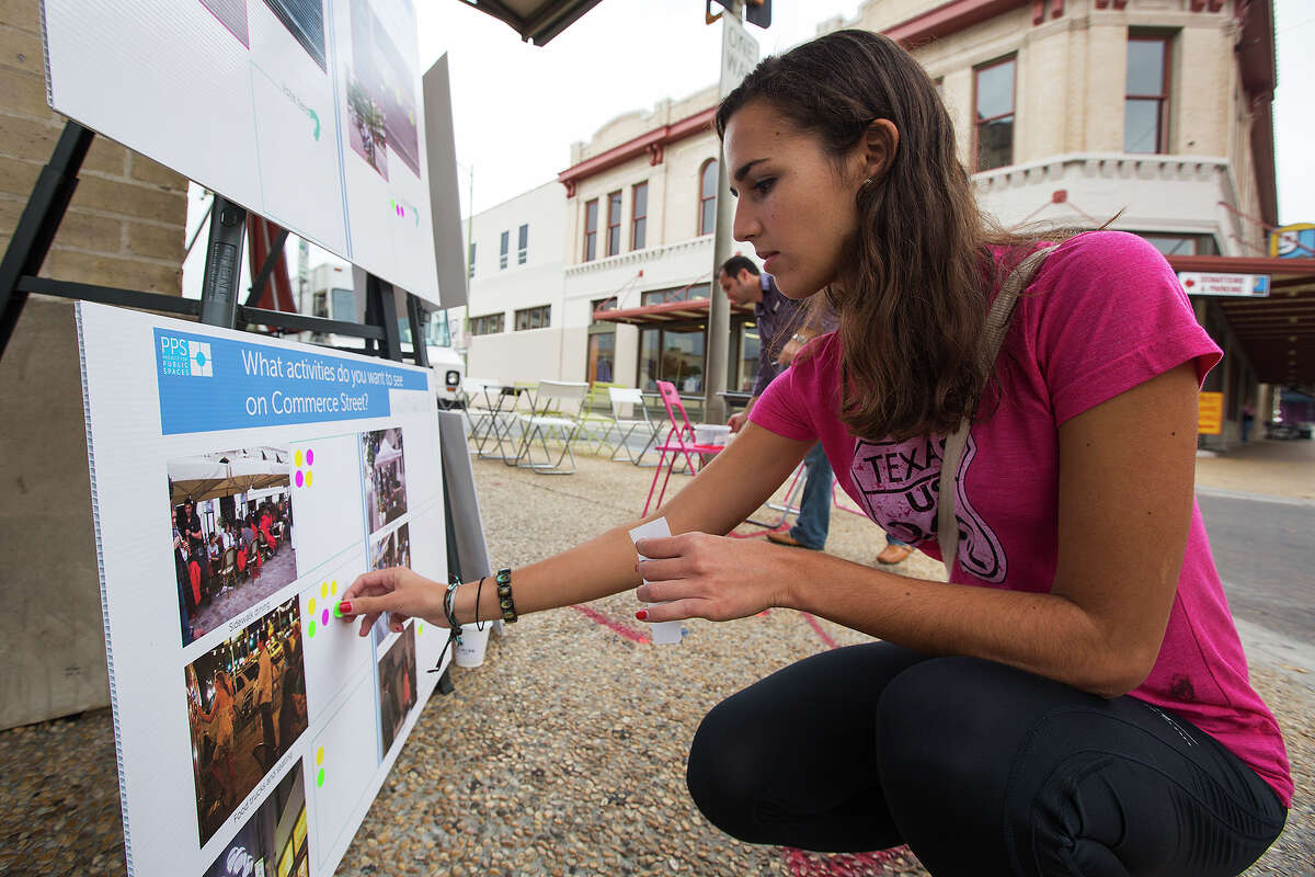 Alexandra Wilcox places stickers on activities she would like to see on Commerce Street during a