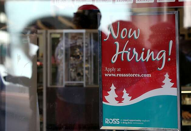 A sign outside an Express clothing store in New York advertises for workers, seen on
