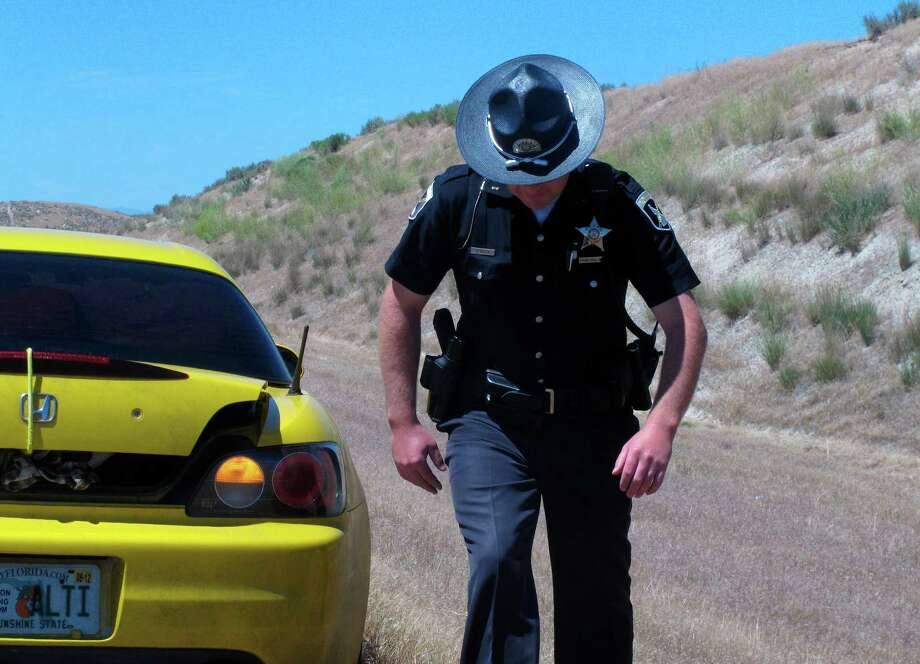 In this photo taken June 20, 2012, Idaho State Police Trooper Justin Klitch walks away from a car he stopped on the Idaho-Oregon border in Fruitland, Idaho.  As the Evergreen state works out the various complications of its new law,  including the fact that marijuana is still illegal under federal law, neighbors of Washington are watching with curiosity, and perhaps some apprehension. Idaho officials already have their hands full with Idahoans obtaining medical marijuana cards out of state. The Gem State borders three medical marijuana states, a reality that has caused medical marijuana arrests to outpace those of traffickers or other users. Although Idaho is a largely conservative state, there are pockets defined by borders and demographics that could create new challenges for law enforcement.  (AP Photo/Nigel Duara) Photo: Nigel Duara, STF / AP