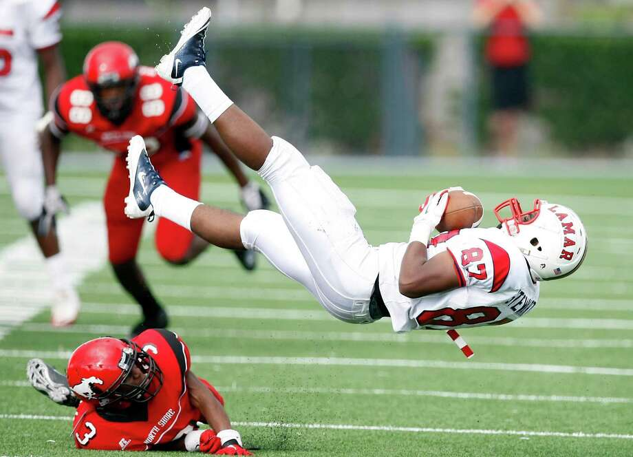 Lamar high school's Joshua Stewart, top, holds on to the ball after being tackled by North Shore High School's Chris Russell during the first quarter of a 5A Division Region III final, Saturday, Dec. 8, 2012, in Veterans Memorial Stadium in Pasadena. Photo: Nick De La Torre, Houston Chronicle / © 2012  Houston Chronicle