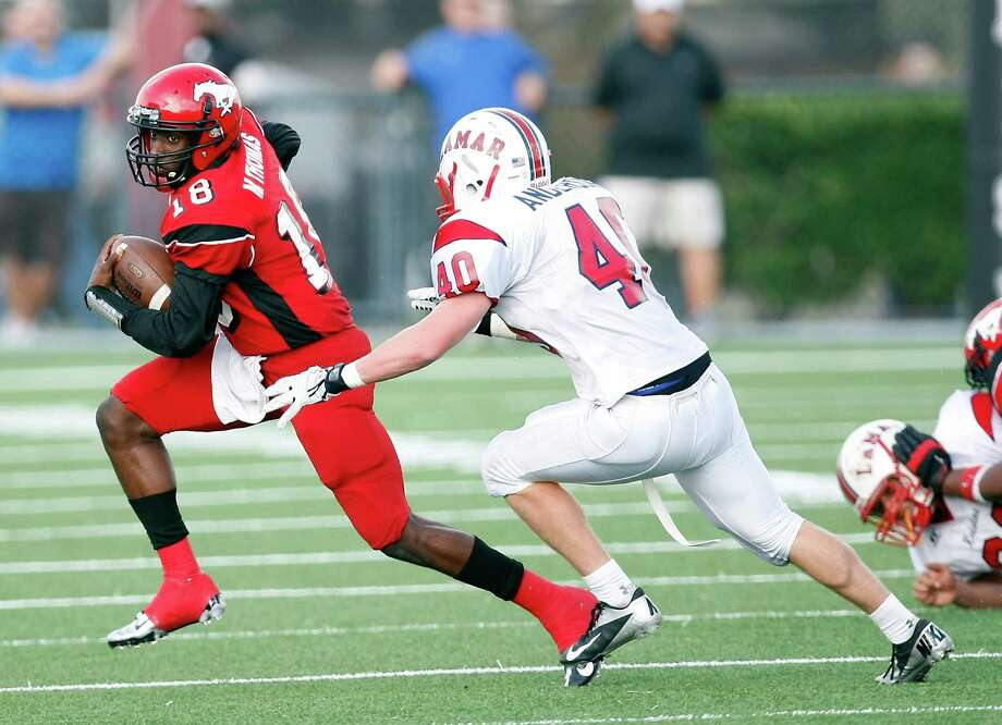 North Shore High School's Micah Thomas gets away from Lamar High School's Jack Anderson for a first down during the second quarter of a 5A Division Region III final, Saturday, Dec. 8, 2012, in Veterans Memorial Stadium in Pasadena. Photo: Nick De La Torre, Houston Chronicle / © 2012  Houston Chronicle