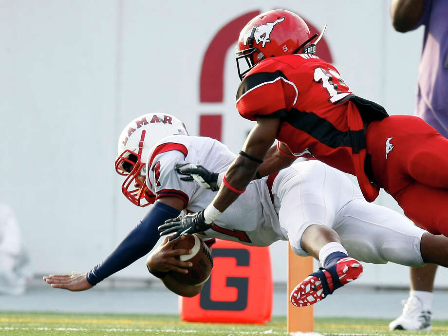 Darrell Colbert of Lamar High School dives for the end zone for a touchdown as North Shore High School's Jomal Wiltz tries to stop him during the fourth quarter of a 5A Division Region III final, Saturday, Dec. 8, 2012, in Veterans Memorial Stadium in Pasadena. Photo: Nick De La Torre, Houston Chronicle / © 2012  Houston Chronicle