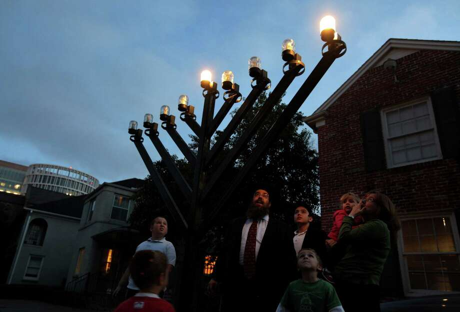 Rabbi Lazer Lazaroff turns on the Menorah while his family stands by while he tests the light bulbs of the large Outdoor Menorah Thursday, Dec. 6, 2012, in Houston in preparation for the first day of Chanukah on Saturday at night fall. Photo: Mayra Beltran, Houston Chronicle / © 2012 Houston Chronicle