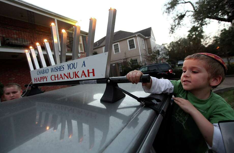 Levi Lazaroff, 3, helps his father and brother attach the Chanukah decoration on their vehicle in preparation for the first day of Chanukah on Saturday at night fall on Thursday, Dec. 6, 2012, in Houston. Photo: Mayra Beltran, Houston Chronicle / © 2012 Houston Chronicle
