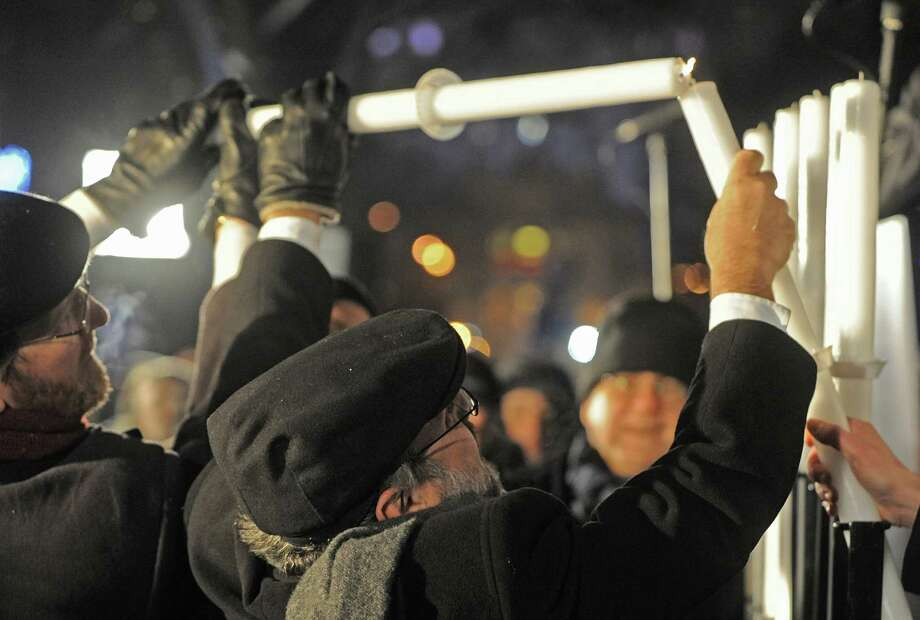 Poland's chief rabbi Michael Schudrich, center, lights the first candle celebrating the beginning of Hanukkah, the Jewish festival of lights, on Grzybowski square in Warsaw, Poland, Saturday, Dec. 8, 2012. Photo: Alik Keplicz, Associated Press / AP