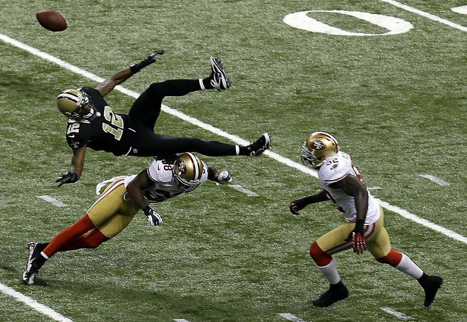 Saints wide receiver Marques Colston (12) is upended by 49ers safety Dashon Goldson (38), causing an interception on Nov. 25. Photo: Bill Haber, Associated Press