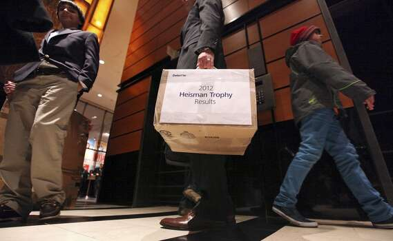 A Heisman official carries a box labled 2012 Heisman Trophy Results into the New York Marriott Marquis hotel in New York, New York Saturday Dec. 8, 2012 before the Heisman winner announcement.