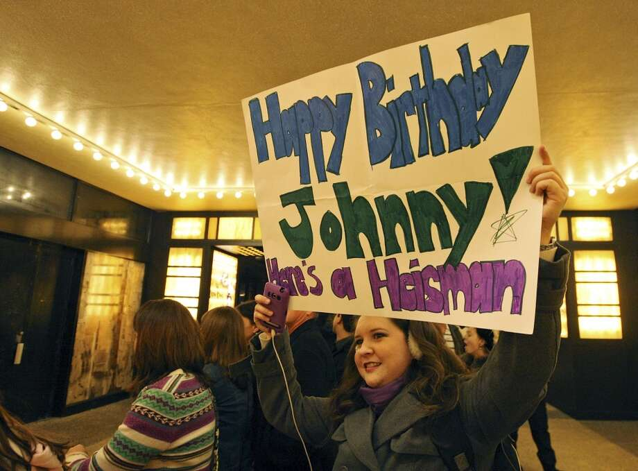 Texas A&M 2004 graduate Natalie Melton, 30 of Corpus Christi, Tx., holds a sign for Heisman finalist Texas A&M's quarterback Johnny Manziel, outside the Best Buy Theater in Times Square before the Heisman winner announcement Saturday Dec. 8, 2012 in New York, New York.