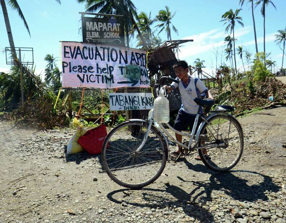 A boy pushes his bicycle loaded with drinking water past a sign near a school serving as an evacuation center for victims of Typhoon Bopha in the town of Maparat in Compostela Valley province on December 8, 2012.  Hungry and homeless typhoon survivors appealed for help on December 8 as the ravaged southern Philippines mourned its more than 500 dead and desperate people in one hard-hit town looted shops in search of food. Photo: TED ALJIBE, AFP/Getty Images / AFP