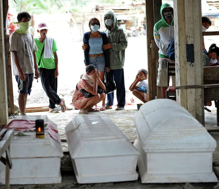 Residents, with their faces covered with masks, stand next to coffins of deceased relatives who died during flash floods caused by Typhoon Bopha, at the former public market in the town of New Bataan in Compostela Valley province on December 8, 2012. Hungry and homeless typhoon survivors appealed for help on December 8 as the ravaged southern Philippines mourned its more than 500 dead and desperate people in one hard-hit town looted shops in search of food. Photo: TED ALJIBE, AFP/Getty Images / AFP