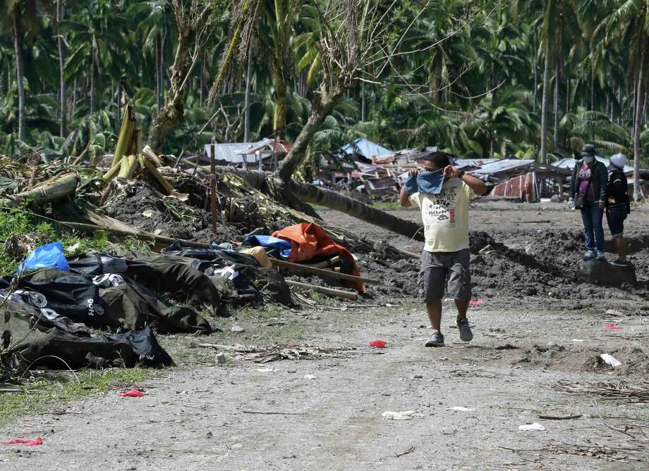 A resident covers his nose as he walks past typhoon Bopha's victims which are left unattended at New Bataan township, Compostela Valley in southern Philippines Saturday Dec. 8, 2012. Search and rescue operations following typhoon Bopha that killed nearly 600 people in the southern Philippines have been hampered in part because many residents of this ravaged farming community are too stunned to assist recovery efforts, an official said Saturday. Photo: Bullit Marquez, Associated Press / AP