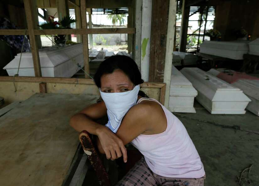 Arlene Barcelona sits at a damaged public market for the wake of her mother Felicitas who was killed