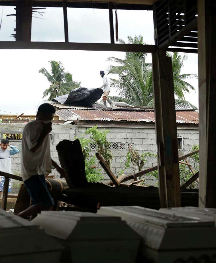 A resident fixes the roof of his house in the background as an unidentified relative prepares to identify typhoon Bopha's victims at a damaged public market which now serves as a makeshift mortuary at New Bataan township, Compostela Valley in southern Philippines Saturday Dec. 8, 2012. Search and rescue operations following typhoon Bopha that killed nearly 600 people in the southern Philippines have been hampered in part because many residents of this ravaged farming community are too stunned to assist recovery efforts, an official said Saturday. Photo: Bullit Marquez, Associated Press / AP