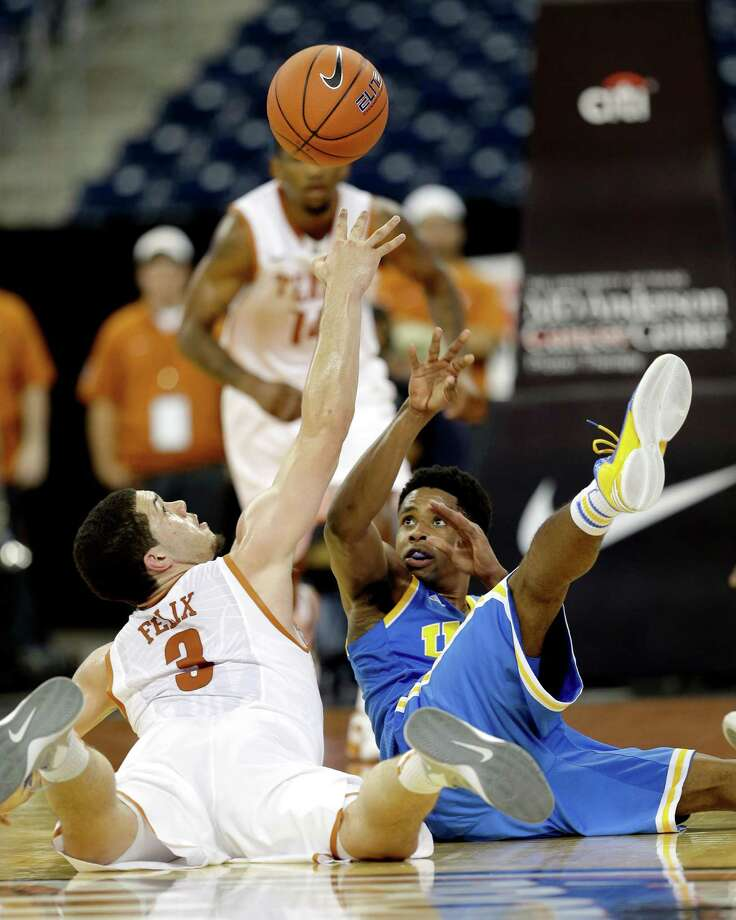 Texas' Javan Felix (3) and UCLA's Larry Drew II, right, reach for a loose ball during the second half of an NCAA college basketball game at Reliant Stadium Saturday, Dec. 8, 2012, in Houston. UCLA beat Texas 65-63. (AP Photo/David J. Phillip) Photo: David J. Phillip, Associated Press / AP