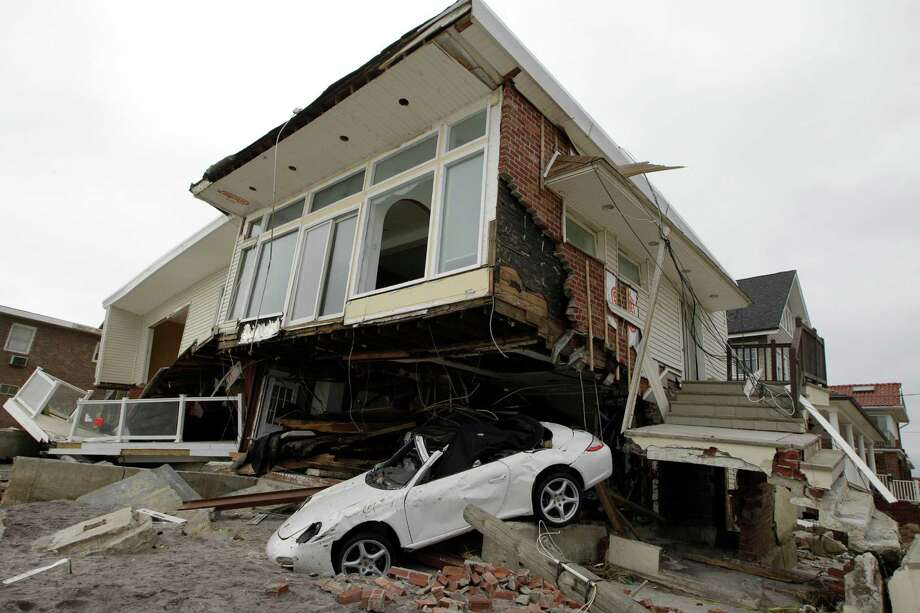 FILE - In this Nov. 19, 2012 file photo, a beachside house, deemed uninhabitable by the New York City Department of Buildings, is left in ruins in the Belle Harbor neighborhood of the Rockaways, in New York. More than three decades before Superstorm Sandy, a state law and a series of legislative reports began warning New York politicians to prepare for a storm of historic proportions, spelling out scenarios eerily similar to what actually happened. (AP Photo/Kathy Willens, File) Photo: Kathy Willens