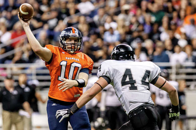 Brandeis quarteback Brian Chapman gets off a pass as Steele's Josh Malin applies pressure during the third quarter of their Class 5A Division II state quarterfinal game at the Alamodome on Dec. 8, 2012.  Steele won the game 28-12. Photo: Marvin Pfeiffer, San Antonio Express-News / Express-News 2012