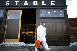 Workers from Servicemaster Restoration Services carry out buckets of standing water from the kitchen area of Stable Cafe on Folsom St.  Business on the 2100 block of Folsom St. in San Francisco were flooded this morning by water that backed up through the sewage lines.  Sunday December 2nd, 2012.