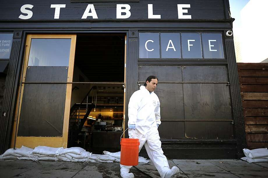 Buckets of water are hauled from the Stable Cafe on Folsom Street after heavy rains led to flooding. Photo: Michael Short, Special To The Chronicle