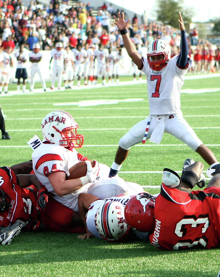Much to the delight of teammate Darrell Colbert (7), Cory Mitchell scores a third-quarter touchdown for Lamar on a 1-yard plunge Saturday. Photo: Nick De La Torre, Staff / © 2012  Houston Chronicle