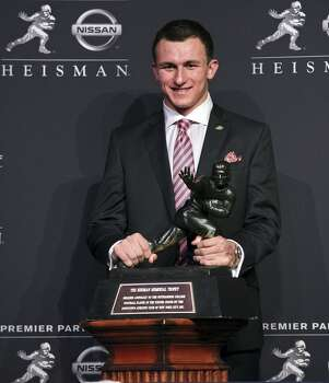 Heisman finalist Texas A&M's quarterback Johnny Manziel poses for photos during a press conference before the Heisman winner announcement Saturday Dec. 8, 2012 at the New York Marriott Marquis hotel in New York, New York.