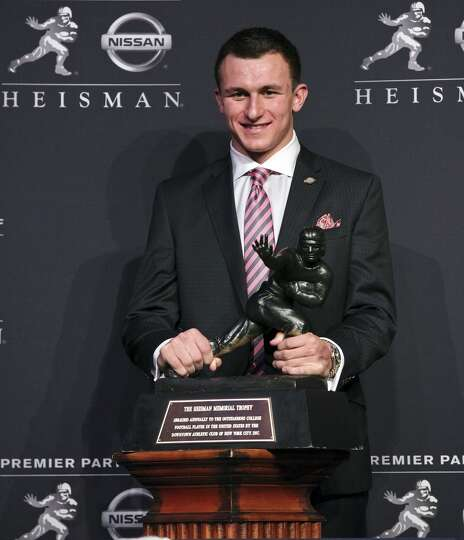 Heisman finalist Texas A&M's quarterback Johnny Manziel poses for photos during a press conference b