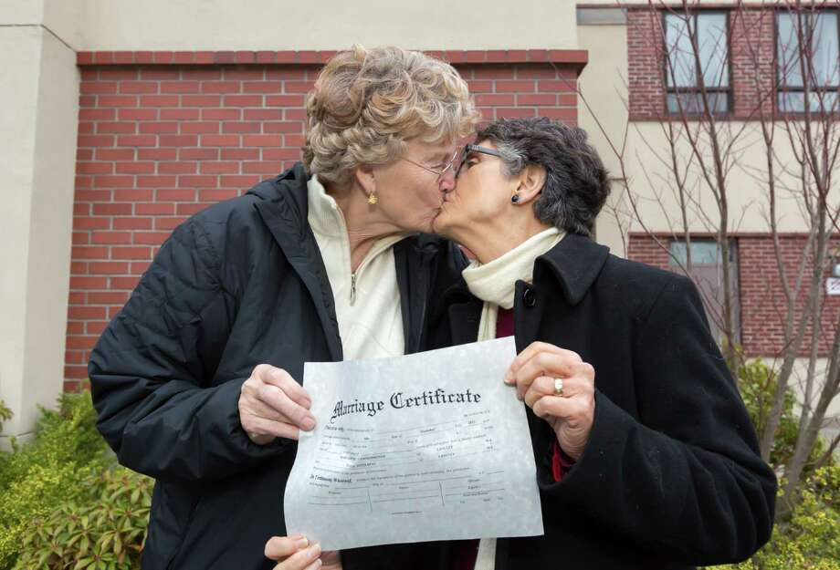 In this photo provided by Richard Wood, retired Army Col. Grethe Cammermeyer, left, kisses Diane Divelbess, her partner of 24 years, as they pose for photos after the two received their marriage license Thursday, Dec. 6, 2012, in Coupeville, Wash. Two retired military women who fought for the rights of gays in the military were among the hundreds of couples who received their marriage licenses this week as Washington state's voter-approved law allowing same-sex marriage took effect. Former Air Force flight nurse Maj. Margaret Witt, of Spokane, and Cammermeyer, of Whidbey Island, both successfully challenged the military's ban on open service by gays and lesbians. They were first in line on Thursday in their home counties to receive their licenses with their partners as the law took effect. (AP Photo/ kapchur.us photography, Richard Wood) Photo: Richard Wood