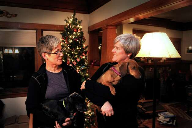 "Former Army Major Margaret Witt, right, and Lori Johnson, left, stand in their south hill home, Monday, Dec. 3, 2012 in Spokane, Wash. They are planning to marry in a few weeks after receiving one of the first marriage licenses for same sex couples this week. Witt fought the Air Force over ""Don't Ask, Don't Tell"" and was with President Obama when he signed the repeal.  (AP Photo/The Spokesman-Review, Jesse Tinsley)  COEUR D'ALENE PRESS OUT Photo: Jesse Tinsley"