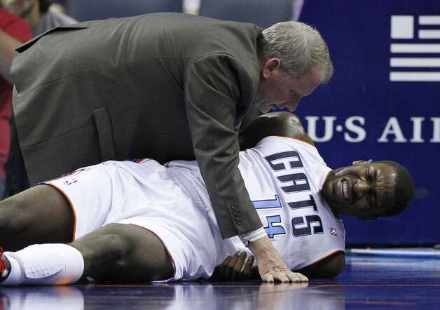 A trainer checks on injured Charlotte Bobcats' Michael Kidd-Gilchrist (14) during the first half of an NBA basketball game against the San Antonio Spurs in Charlotte, N.C., Saturday, Dec. 8, 2012. (AP Photo/Chuck Burton) (Chuck Burton / Associated Press)