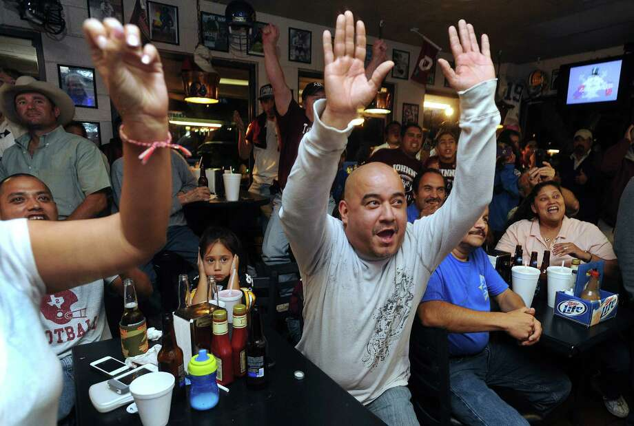 Joey Lopez, middle, and other fans of Texas A&M quarterback Johnny Manziel celebrate as the announcement is made on television at the Wing King restaurant in Kerrville that Manziel has won the Heisman trophy on Saturday night, Dec. 8, 2012. Manziel played high school football for Tivy High School in Kerrville. Photo: Billy Calzada, San Antonio Express-News / SAN ANTONIO EXPRESS-NEWS