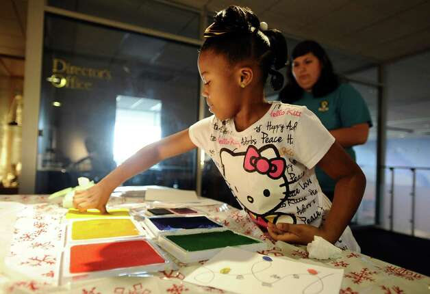 Nyavia Harrison, 6, of Port Arthur gets her hands dirty with the thumb print Christmas lights craft table at the Museum of the Gulf Coast for Sleigh Bells Ring! in Port Arthur on Saturday, December, 8 2012. Photo taken: Randy Edwards/The Enterprise Photo: Randy Edwards