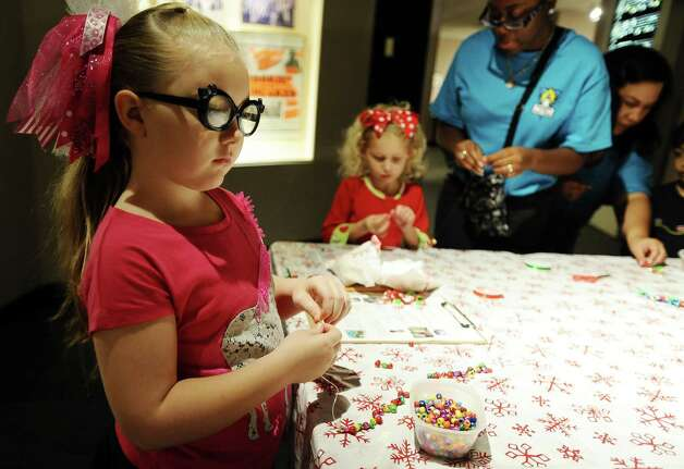 Graciie Jacobs, 6, makes a bracelet at the activity table at the Museum of the Gulf Coast for Sleigh Bells Ring! in Port Arthur on Saturday, December, 8 2012. Photo taken: Randy Edwards/The Enterprise Photo: Randy Edwards